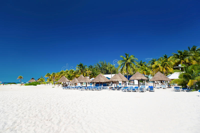 Caribbean beach with sun umbrellas and bed royalty free stock images