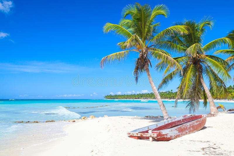 Caribbean Sea coast, Dominican republic. Coconut palms and old red pleasure boat are on white sandy beach. Caribbean Sea, Dominican republic landscape, Saona royalty free stock photo