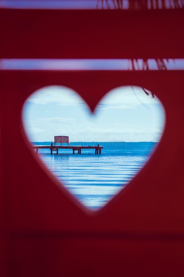 Caribbean Sea through Red Beach Bench Hearts stock photography