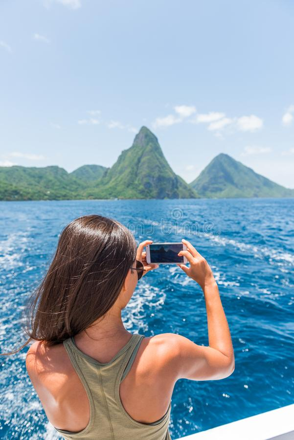 Caribbean travel girl taking photo with phone on St Lucia Pitons boat cruise ride in tropical vacation summer lifestyle royalty free stock image