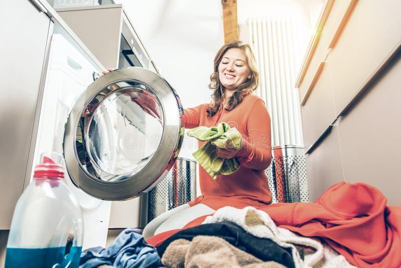 Caricamento della donna che lava machineWoman che carica i vestiti sporchi in lavatrice per il lavaggio immagini stock