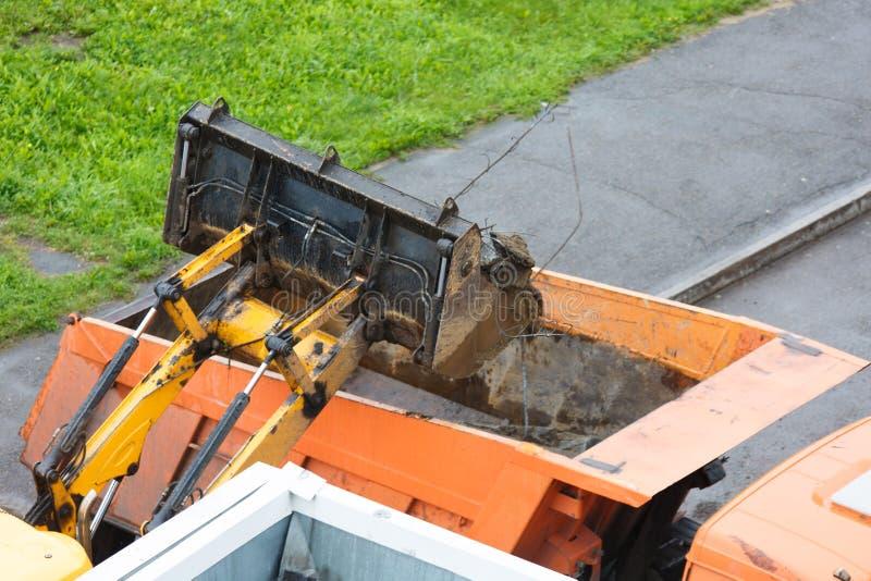Caricamento di detriti da costruzione nel camion per il loro trasferimento nella discarica immagine stock libera da diritti
