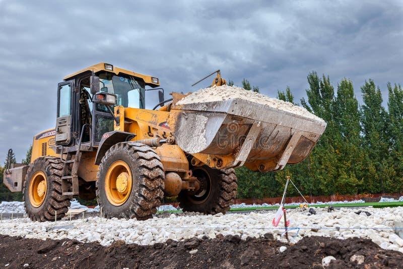 Caricamento pesante del bulldozer e ghiaia commovente sul sito della costruzione di strade fotografia stock