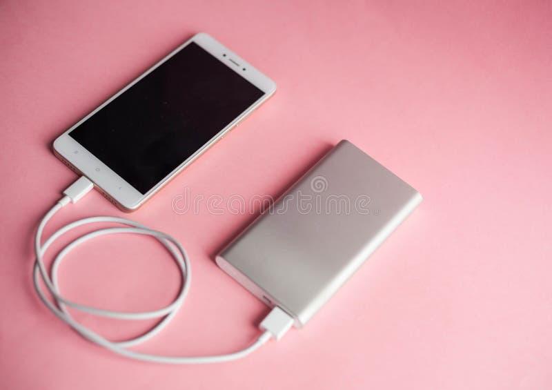 Caricatore bianco dello Smart Phone con la banca di potere del caricatore su fondo rosa immagini stock