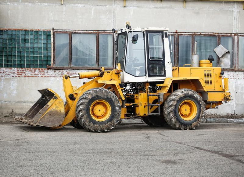 Caricatore resistente del bulldozer della ruota sui precedenti di paesaggio industriale fotografia stock