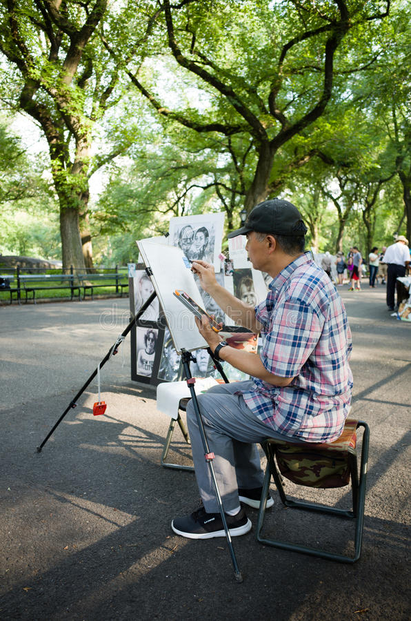 Caricaturist on The Mall in Central park drawing. Caricaturist in Central park drawing - July 17, 2016, The Mall, New York City, NY, USA royalty free stock image