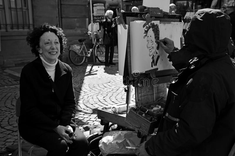 Caricaturist performing on street. Black and white image with a cartoonist while drawing a caricature of a woman. The result was satisfying both for the lady and royalty free stock photo