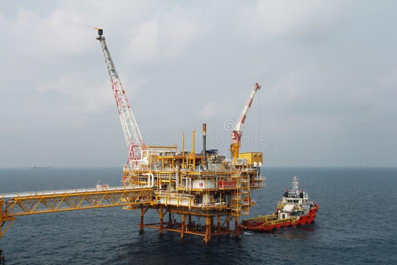 Carico di trasferimento della barca del rifornimento ad olio e industria del gas e carico commovente dalla barca alla piattaforma fotografia stock