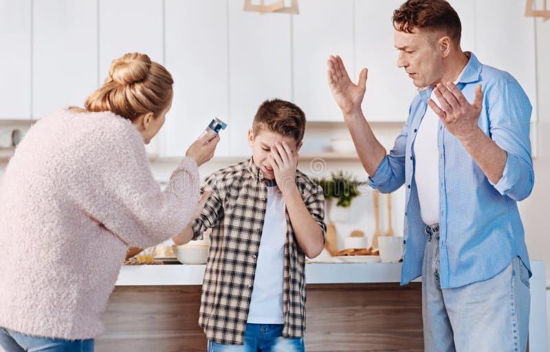 Carign parents castigar a su hijo en la cocina fotografía de archivo libre de regalías