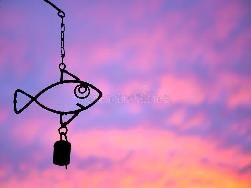Carillón de viento de los pescados con puesta del sol púrpura y anaranjada fotos de archivo libres de regalías