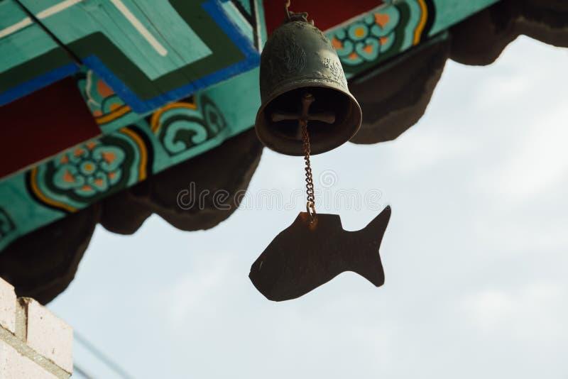 Carillon de vent accrochant sous les gouttières du temple coréen photographie stock