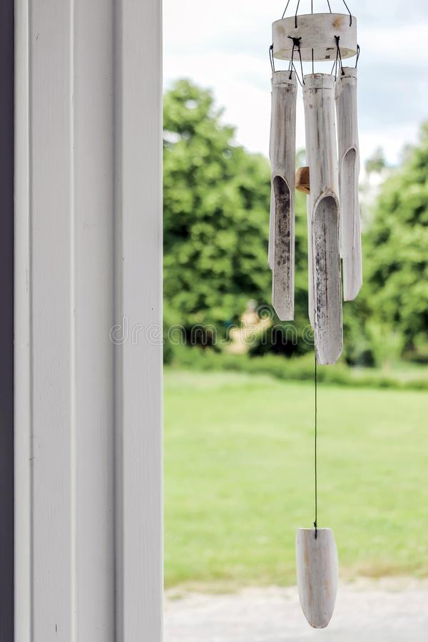 Carillon de vent blanc avec les plantes vertes photographie stock