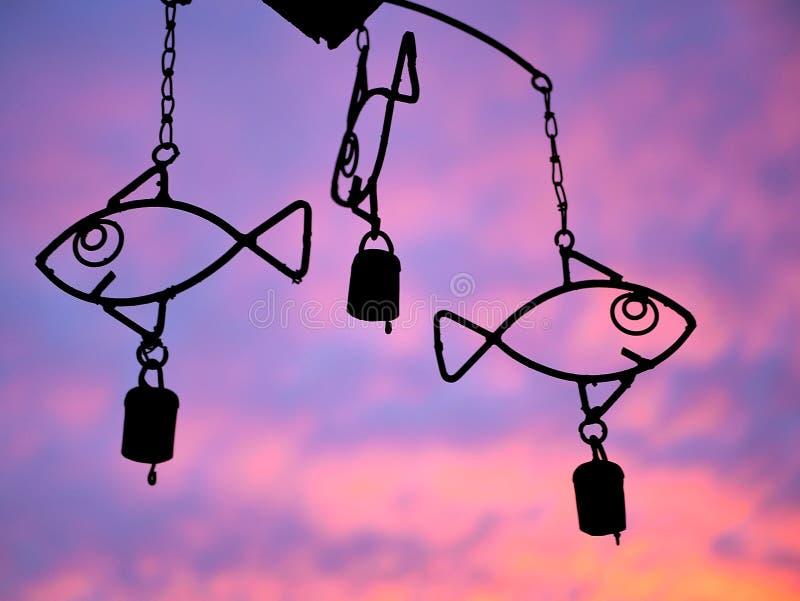 Carillon de vent de poissons avec le coucher du soleil pourpre et orange images stock