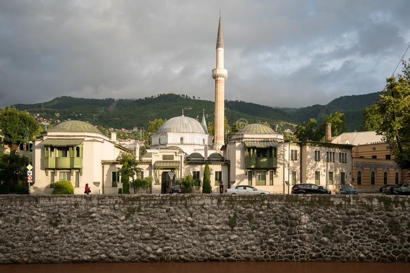 Carina Mosque - Sarajevo. On the oposite bank of the river Miljacka is Viecnica - the City Hall of Sarajevo and National and University Library of Bosnia and stock photography