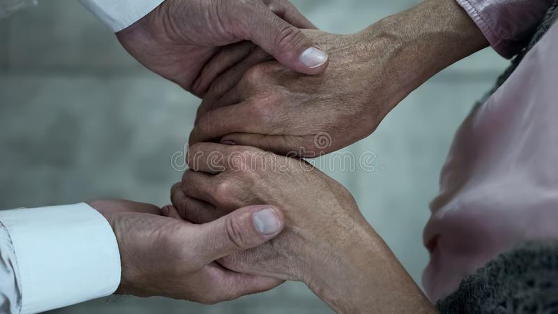 Caring adult son holding mother hands, meeting in nursing home park, family. Stock photo royalty free stock images