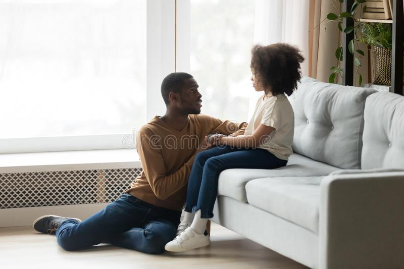 Caring African American father comforting adorable preschool daughter. Caring African American father comforting, supporting upset adorable preschool daughter royalty free stock photography