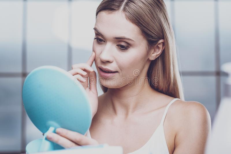 Beautiful young woman looking at her face stock image