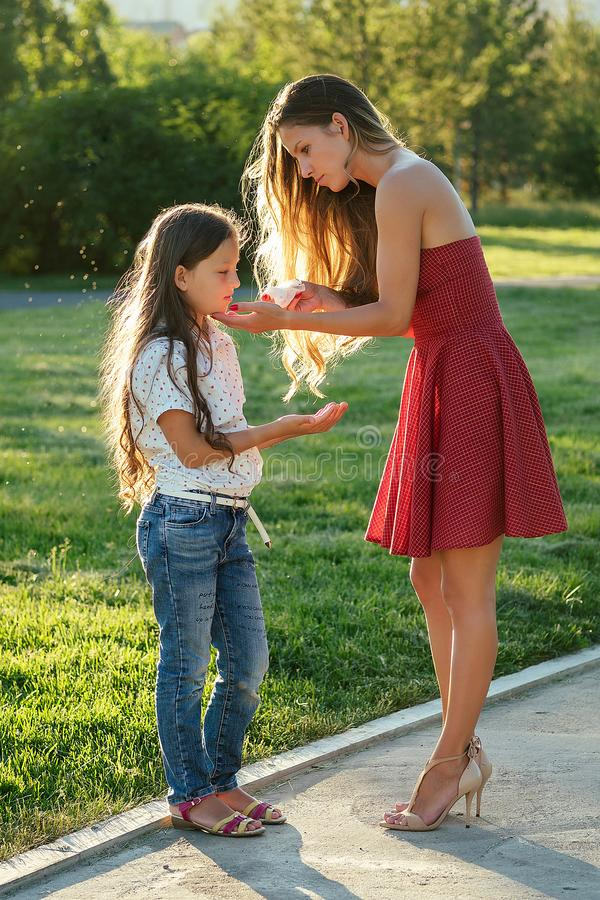 Caring and beautiful long-haired mother in cocktail red dress wipes her daughter`s face with wet napkins in the park in royalty free stock images