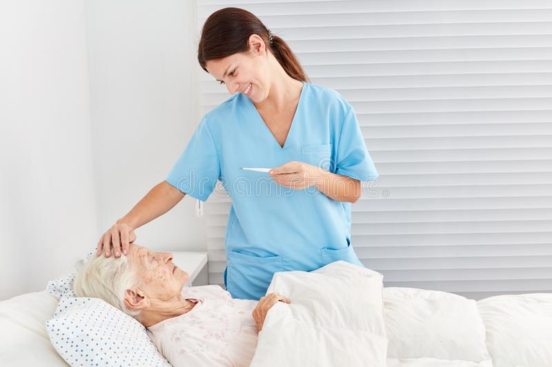 Caring caregiver on fever. Caring nurse with fever measuring a sick patient in ng home royalty free stock image