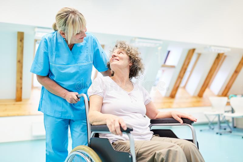 Caregiver takes care of a senior woman. Caring caregiver takes care of a senior women in a wheelchair at rehab stock image
