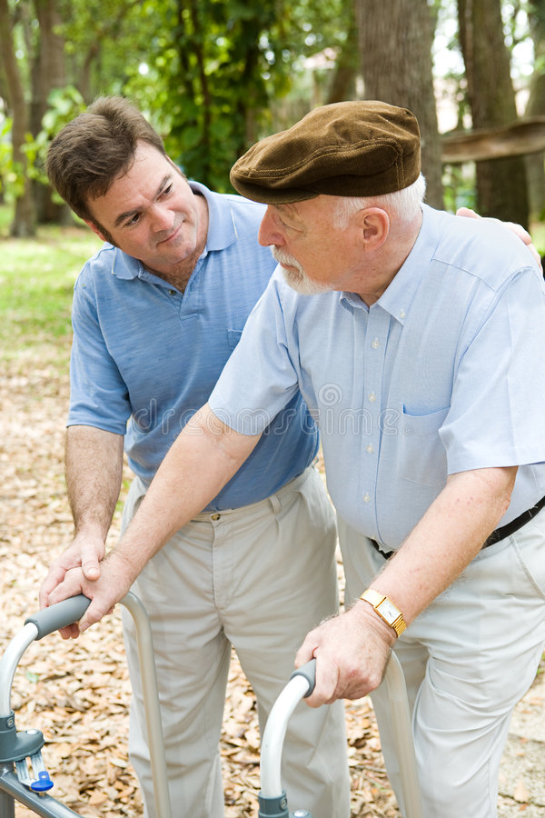 Caring For Dad. Adult son caring for his aging father who is confined to a walker stock image