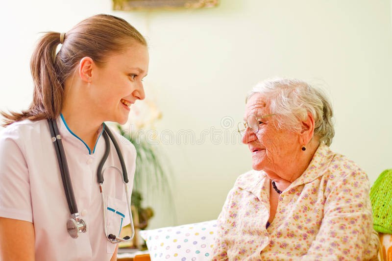Caring doctor with elderly woman stock images