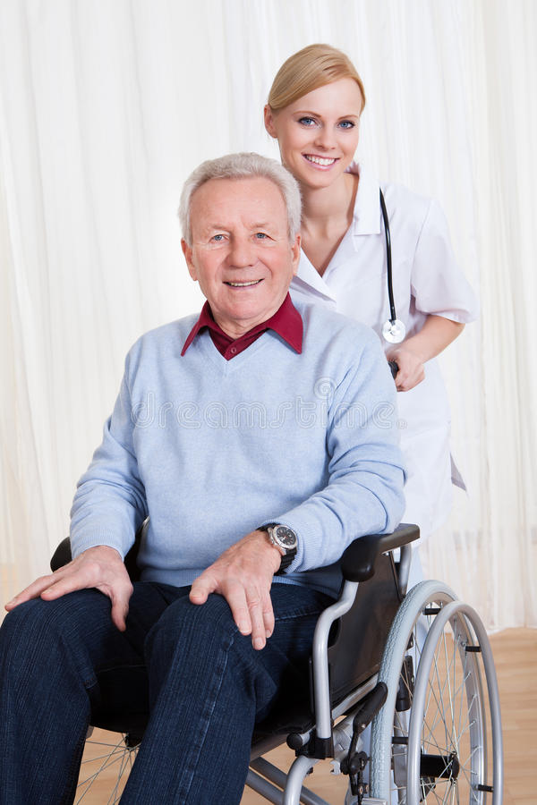 Caring doctor helping handicapped patient stock images