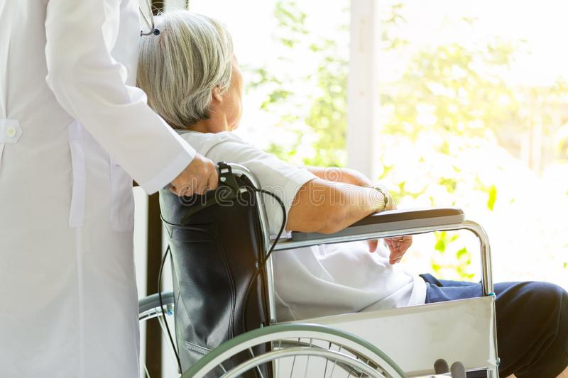 Caring doctor or nurse supporting disabled,alzheimer senior asian woman on wheelchair,female caregiver walking,elderly patient. With depressive symptoms need stock image