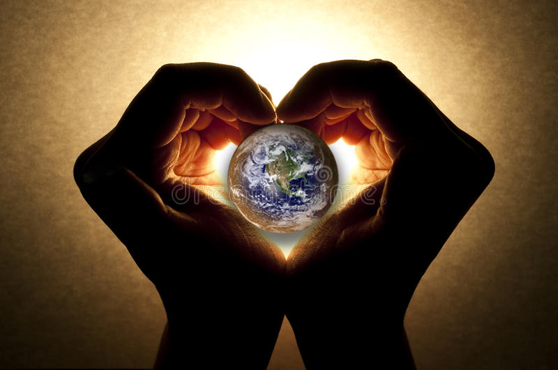 Caring for the earth. Hands and hearts are caring for the earth stock image