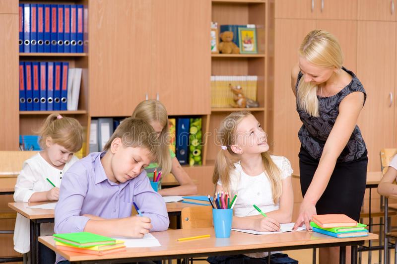 Caring elementary school teacher helping student in classroom stock photography