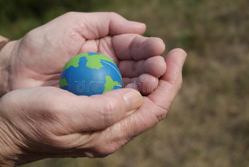Caring for the environment. Eco Friendly Blue and green globe in the palm of hands that are concerned for the environmental conservation royalty free stock photos