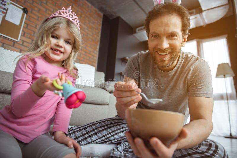 Caring family feeding little baby by porridge stock photo