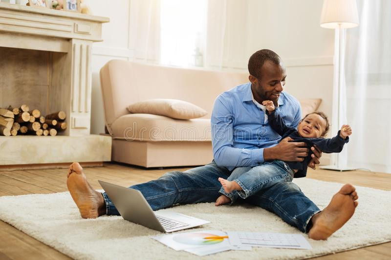 Caring father amusing his little son. Baby crying. Happy caring young smiling father holding a crying baby and amusing his son while sitting on the floor with royalty free stock image