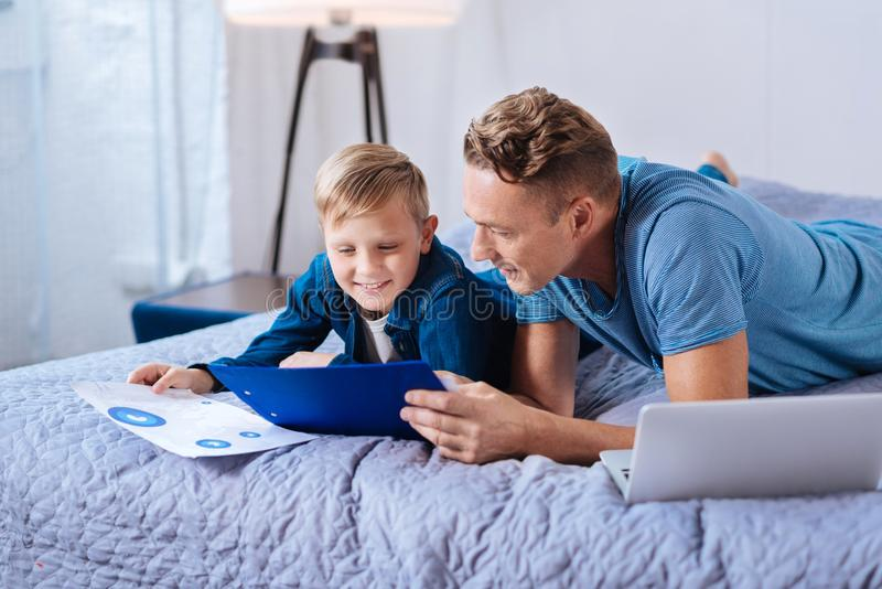 Caring father helping son with his school project royalty free stock image
