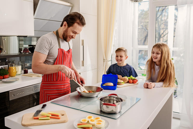 Caring father preparing breakfast for kids stock photos