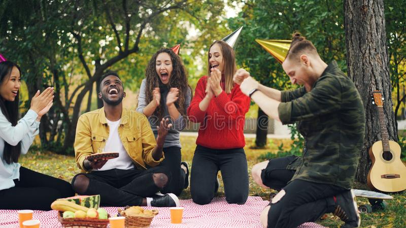 Caring friends are bringing cake to African American man sitting on blanket in park on picnic with closed eyes, he is stock photos