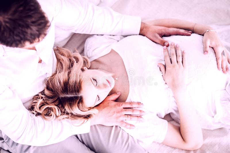 Husband hugs his pregnant wife while sitting on the bed. royalty free stock photography