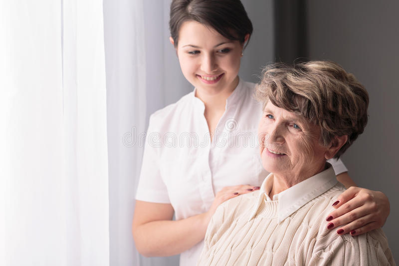 Caring lovely caregiver. Young caring lovely caregiver and happy ward stock photos