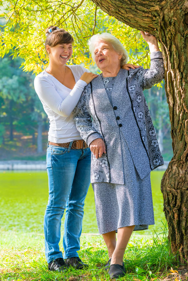 Caring and loving granddaughter walking with her grandmother stock photo