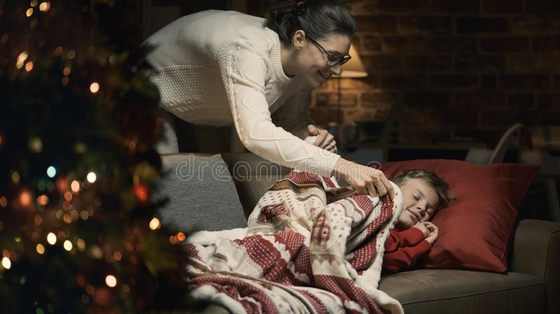 Mother tucking her child on Christmas eve royalty free stock photos
