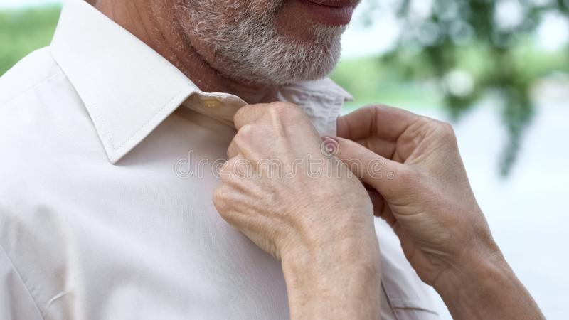 Caring mature lady neatly buttoning husbands shirt, love through ages, support stock photo