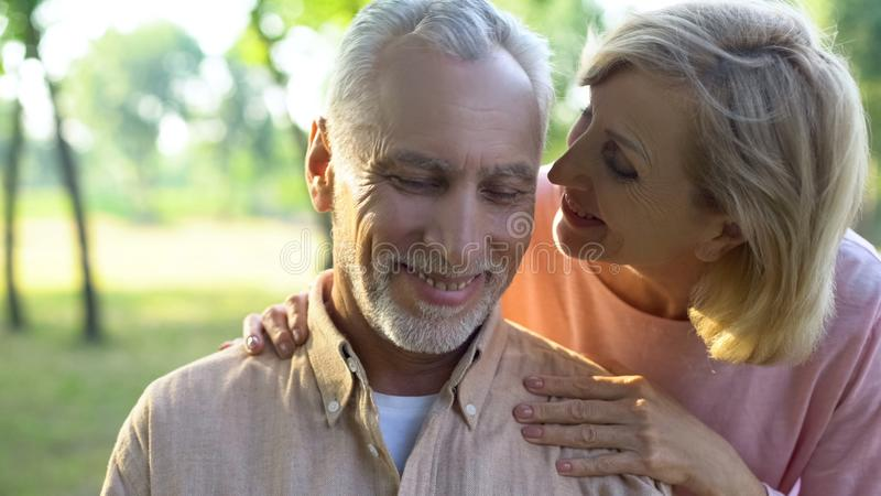 Caring mature wife flirting with handsome husband in park, whispering compliment. Stock photo stock photos