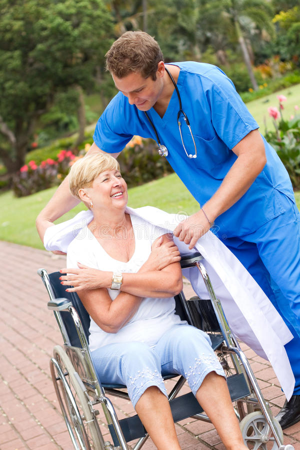 Caring medical staff. Giving his jacket to a senior patient stock photos