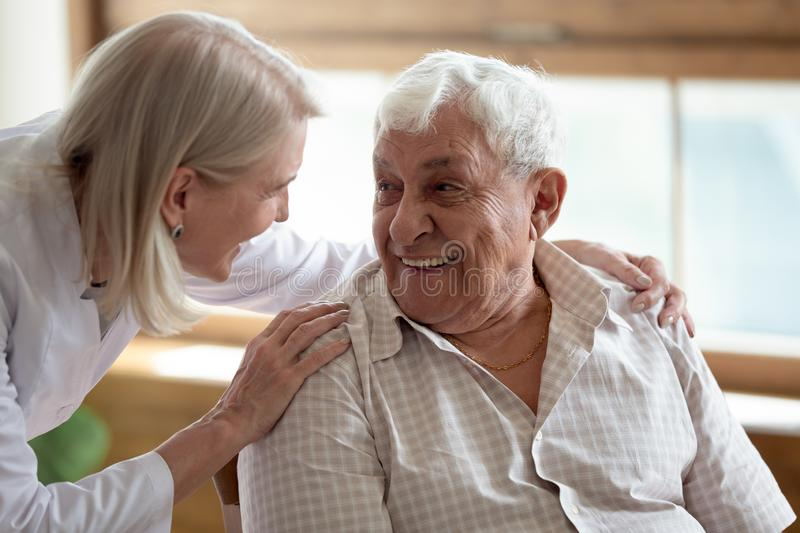 Caring nurse talking to elderly patient 80s man. Caring middle-aged female licensed practical nurse in white coat talk to elderly patient 80s man, worker care royalty free stock photos