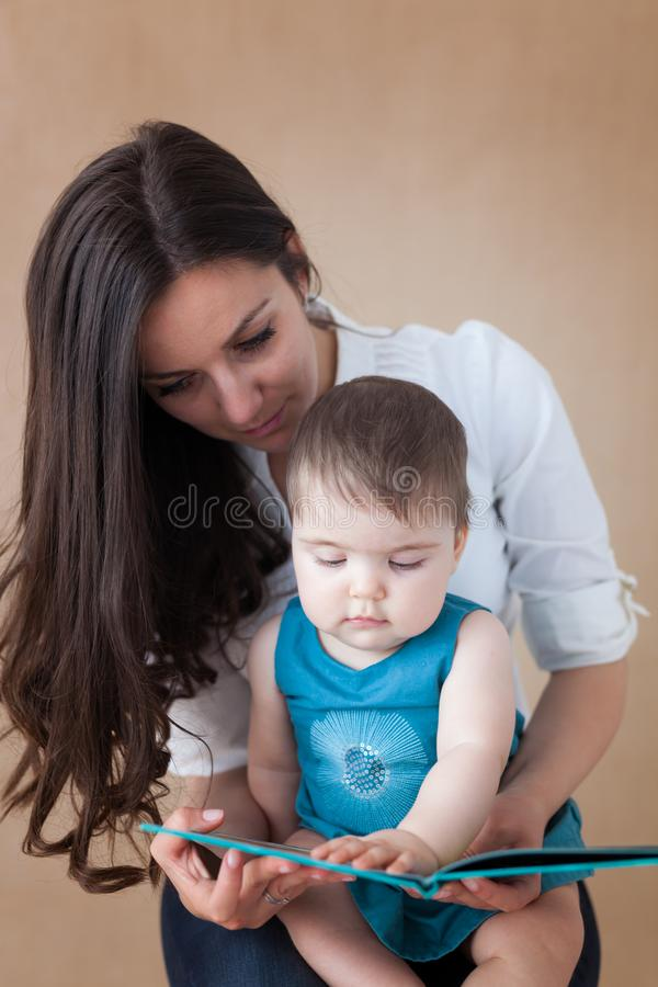 Mother reading a book to her baby girl royalty free stock photos