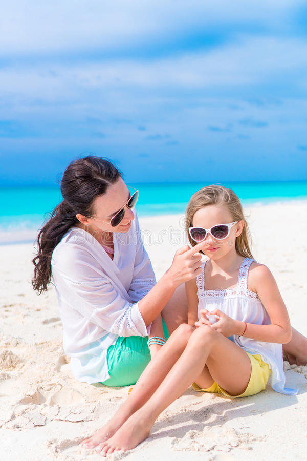 Caring mother applying sun cream to daughter nose on the beach. The concept of protection from ultraviolet radiation royalty free stock image