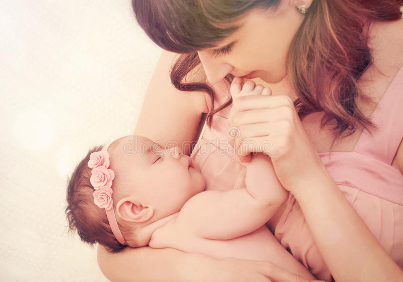 Caring mother kissing fingers of her cute sleeping baby girl royalty free stock image