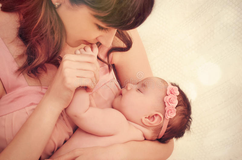 Caring mother kissing little fingers of her cute sleeping baby g. Irl, happy family concept royalty free stock photos