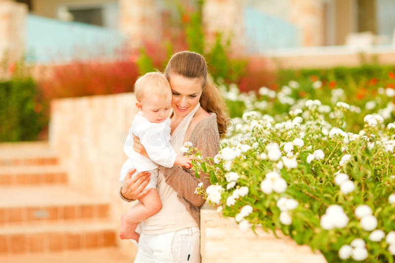 Caring mother showing plants to her baby royalty free stock photo