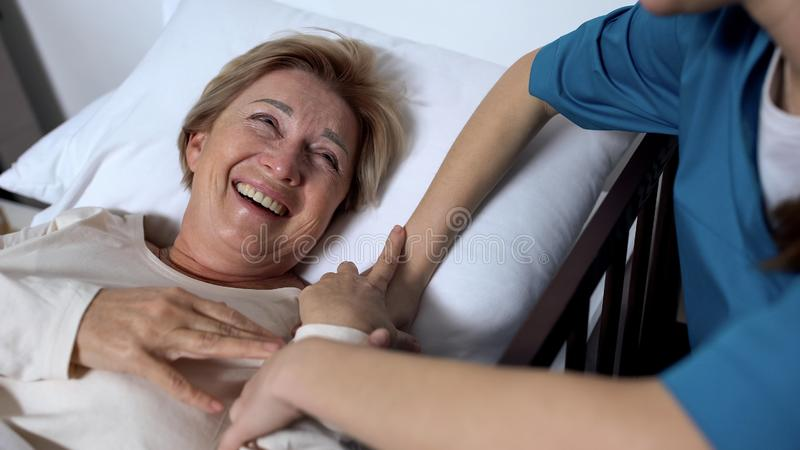 Caring nurse telling jokes to old female patient lying in sickbed rehabilitation. Stock photo stock photography